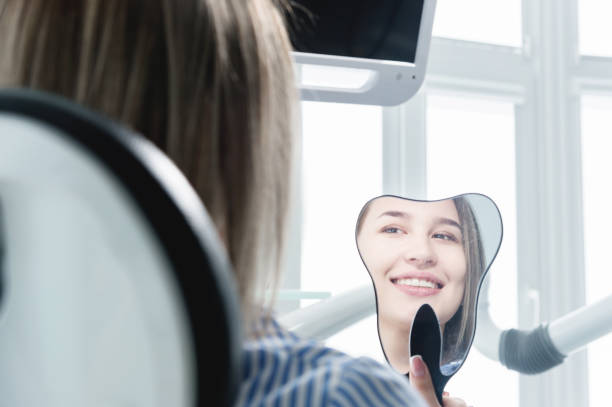Close-up view from the back of a blonde girl sitting in a chair who looks in a tooth-shaped mirror. stock photo