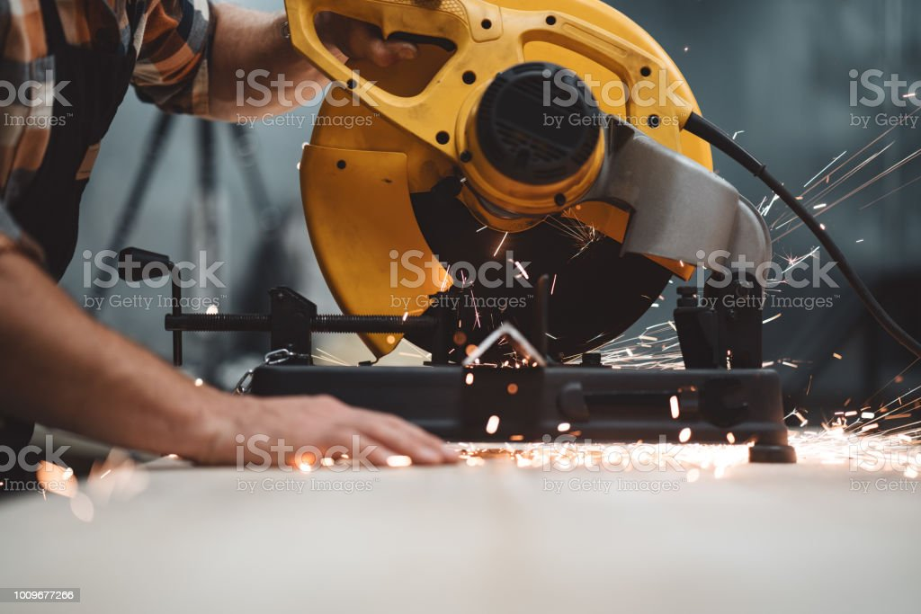 Close-up view hands of mechanic angular grinding machine in action, sparks fly apart. Work in process on metalworking factory. stock photo