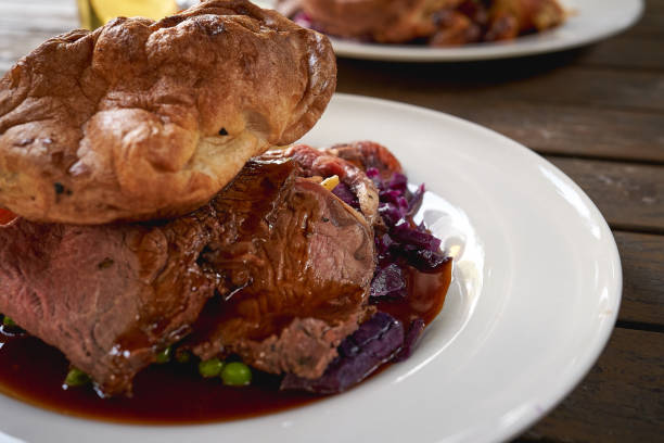 close-up view of a beef sunday roast served with seasonal vegetables and a draft lager beer. - jantar assado imagens e fotografias de stock