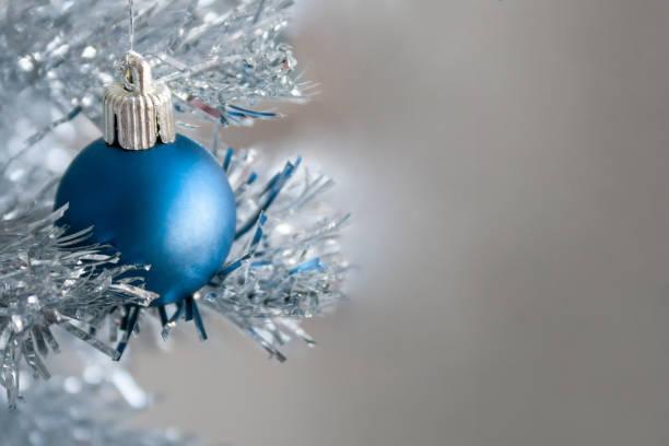 Vue de plan rapproché d'une boule mat bleue s'arrêtant sur un arbre artificiel argenté de Noel avec l'espace de copie pour votre message texte. Mise au point sélective. Fond flou. Décoration à la maison de réveillon du Nouvel An - Photo