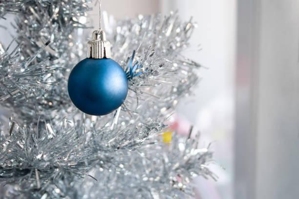 Vue de plan rapproché d'une bille mate bleue s'arrêtant sur un arbre artificiel argenté de Noel - Photo
