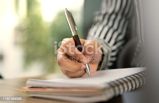 868148002istockphoto Close-up view of a female corporate business hand writing on a notepad with shallow depth of field with warm tones 1152164335