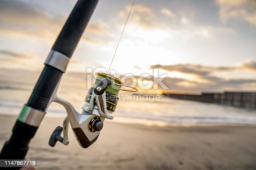 A beautiful sunset on the beach with a closeup of a fishing pole, near the border wall between Tijuana, Mexico, and the United States