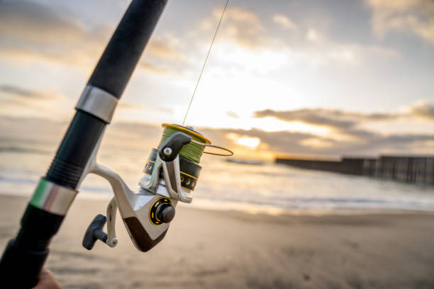 A Close-up View Of A Fishing Pole With The Beach And Waves At Sunset Near The International Border Wall  In Playas Tijuana, Mexico A beautiful sunset on the beach with a closeup of a fishing pole, near the border wall between Tijuana, Mexico, and the United States fishing reel stock pictures, royalty-free photos & images
