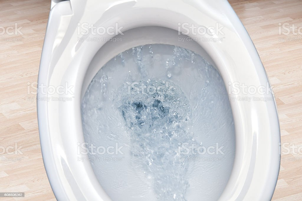 Closeup view of a flushing white toilet bowl. stock photo