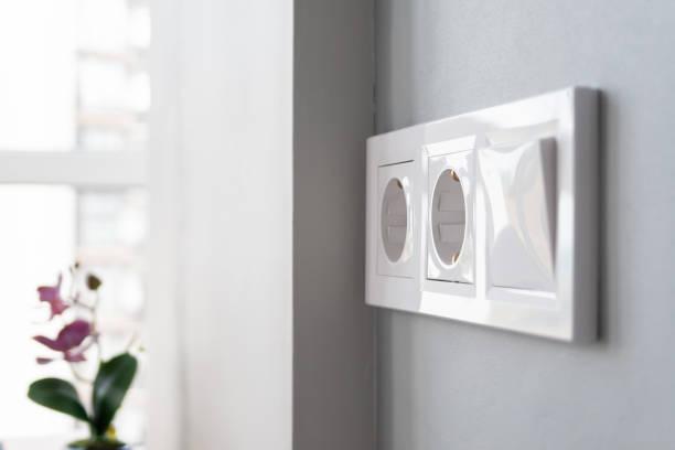 Une vue de plan rapproché d'un groupe de prises électriques européennes blanches et d'un commutateur situé sur un mur gris dans une cuisine moderne légère par la fenêtre. Mise au point sélective. Fond brouillé - Photo