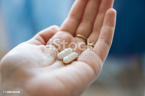 Close-up view of a hand holding two white pills in the palm above a blurry background