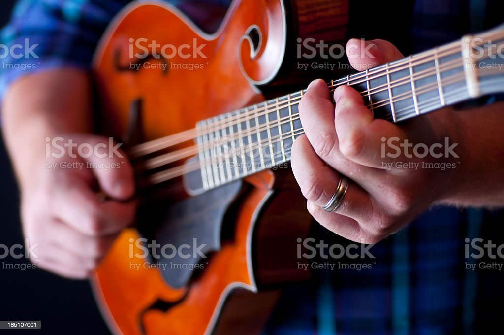 A close-up view of a man playing the mandolin stock photo