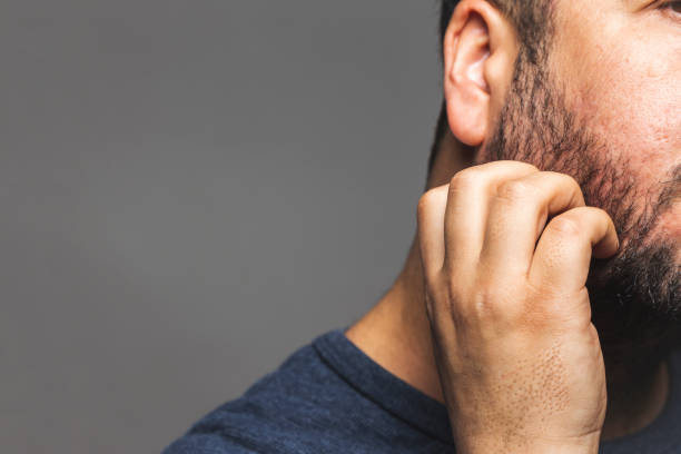 Closeup view of a man scratching beard, thoughtful gesture stock photo