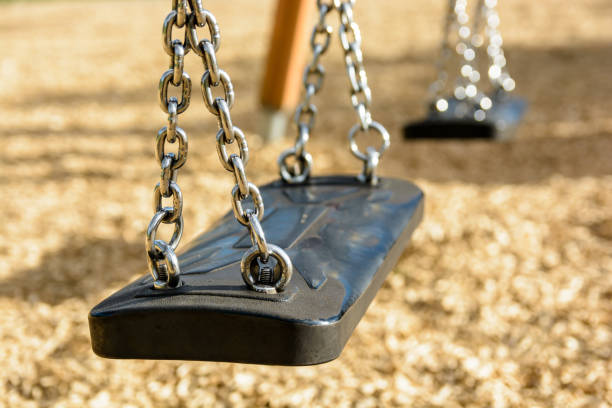 Close-up view of a still child's swing in black plastic in a wood chips covered playground with chrome chains and drop shadow Close-up view of a still child's swing in black plastic in a wood chips covered playground with chrome chains and drop shadow. amortize stock pictures, royalty-free photos & images
