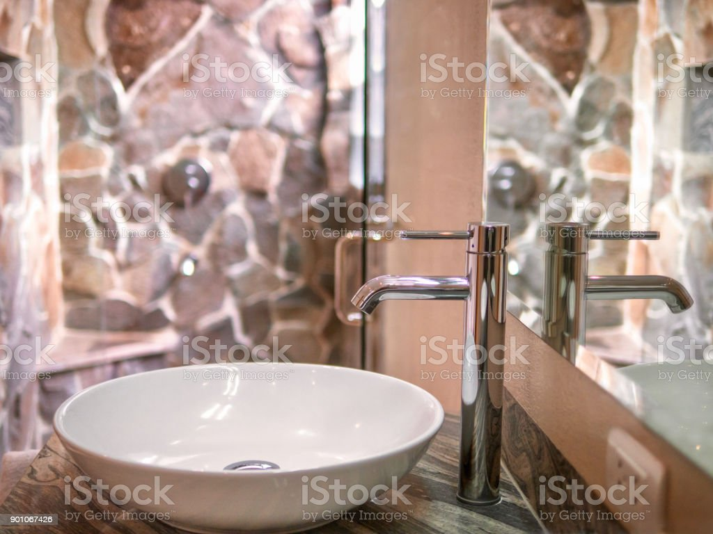 Close-up view of a white round vessel sink and chrome single-hole faucet in bathroom, with reflections in mirror and natural stone shower enclosure in the background. Earth tones and natural light. stock photo