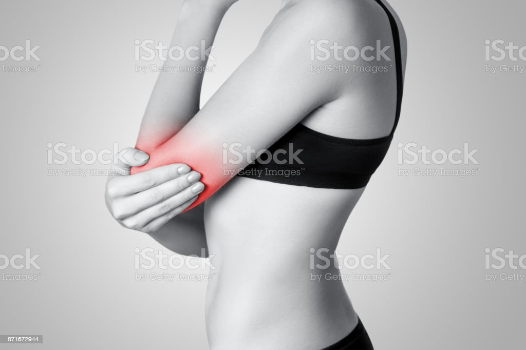 Closeup view of a young woman with elbow pain on gray background. stock photo