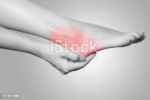 901404510istockphoto Closeup view of a young woman with pain on leg on gray background. 871672998