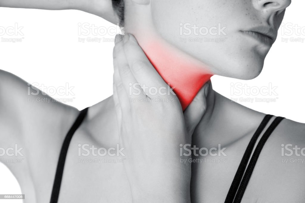 Closeup view of a young woman with pain on neck or thyroid gland.  isolated on white background. Black and white photo with red dot. stock photo