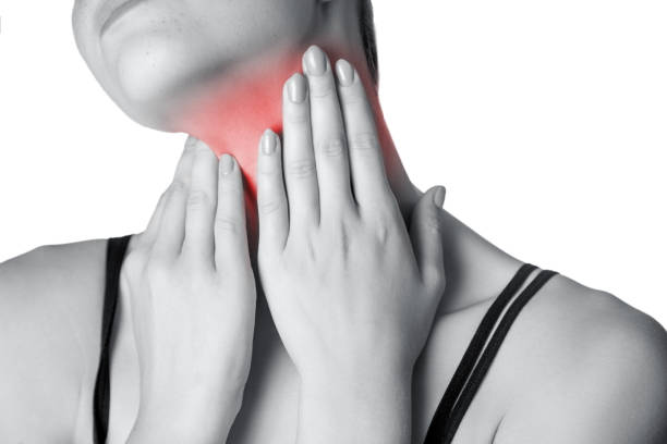 closeup view of a young woman with pain on neck or thyroid gland.  isolated on white background. black and white photo with red dot. - cancer da tireoide - fotografias e filmes do acervo