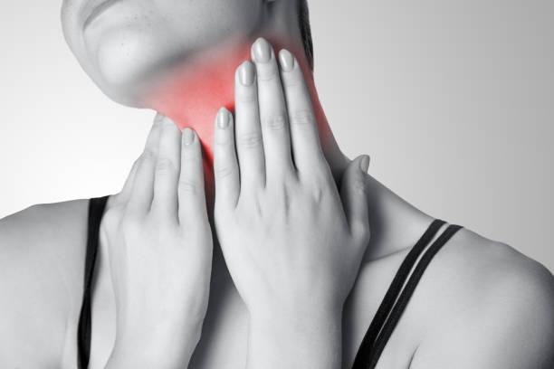 closeup de vista de uma jovem mulher com dor no pescoço ou glândula tireoide em fundo cinza. - cancer da tireoide - fotografias e filmes do acervo