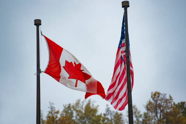 Close-up view of an American flag and a Canadian flag waving in the wind. Close-up view of an American flag and a Canadian flag waving in the wind. geographical border stock pictures, royalty-free photos & images