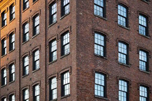 Close-up view of an old residential building with blue sky reflected on the glasses windows. Manhattan, New York City, United States of America.