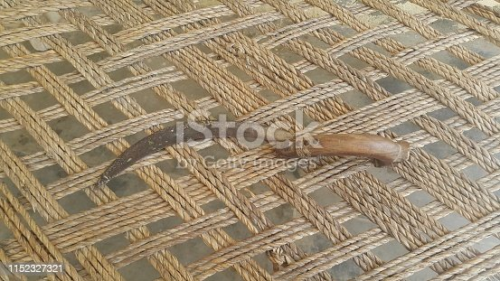 Close-up view of an old sickle (bagging hook or reaping-hook) on the bed surface. Traditional hand-held agricultural tool.