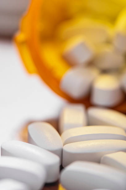 Close-up view of an open Rx pill bottle with white tablets spilling out stock photo