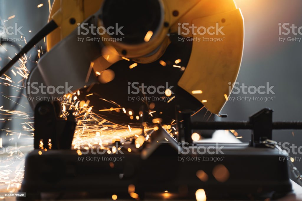 Close-up view of angular grinding machine in action, sparks fly apart. Work in process. Flare effect stock photo