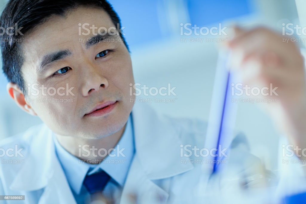Close-up view of asian scientist holding test tube with reagent, laboratory researcher concept stock photo