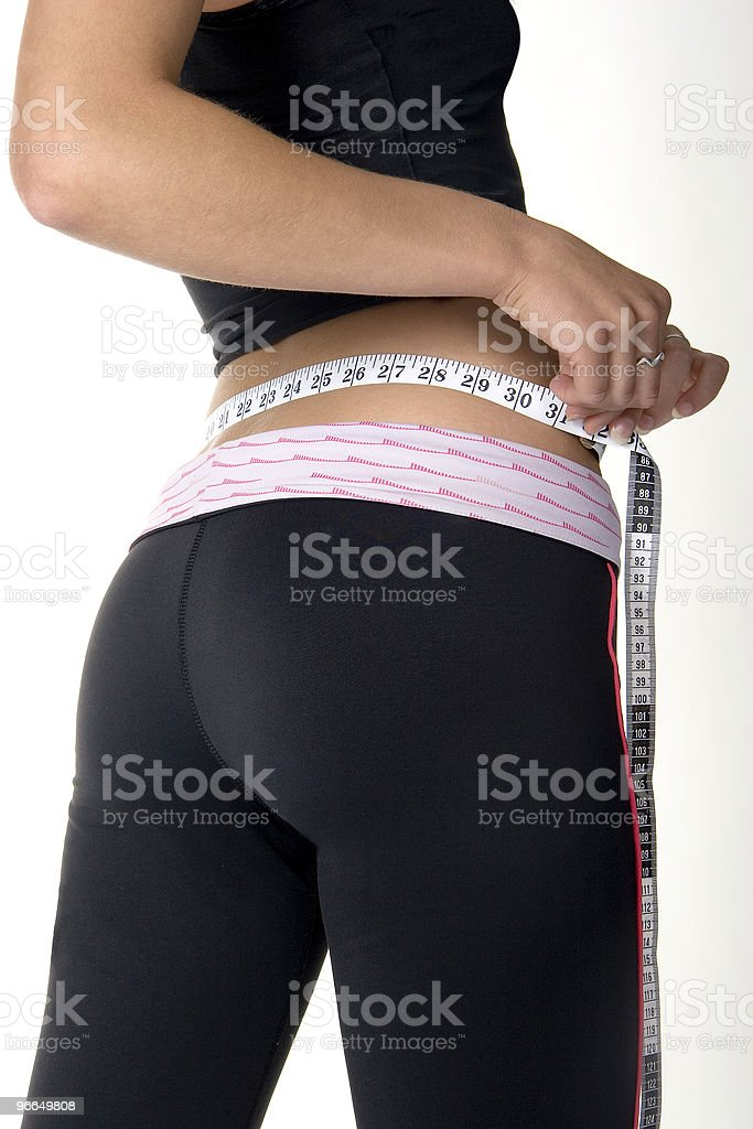 Close-up View of Attractive Young Woman Measuring Her Waist-Line royalty-free stock photo