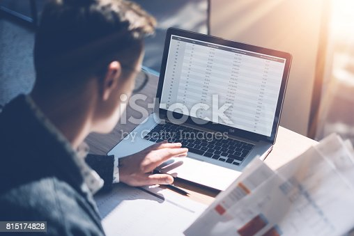 Closeup view of banking finance analyst in eyeglasses working at sunny office on laptop while sitting at wooden table.Businessman analyze stock report on notebook screen.Blurred background,horizontal