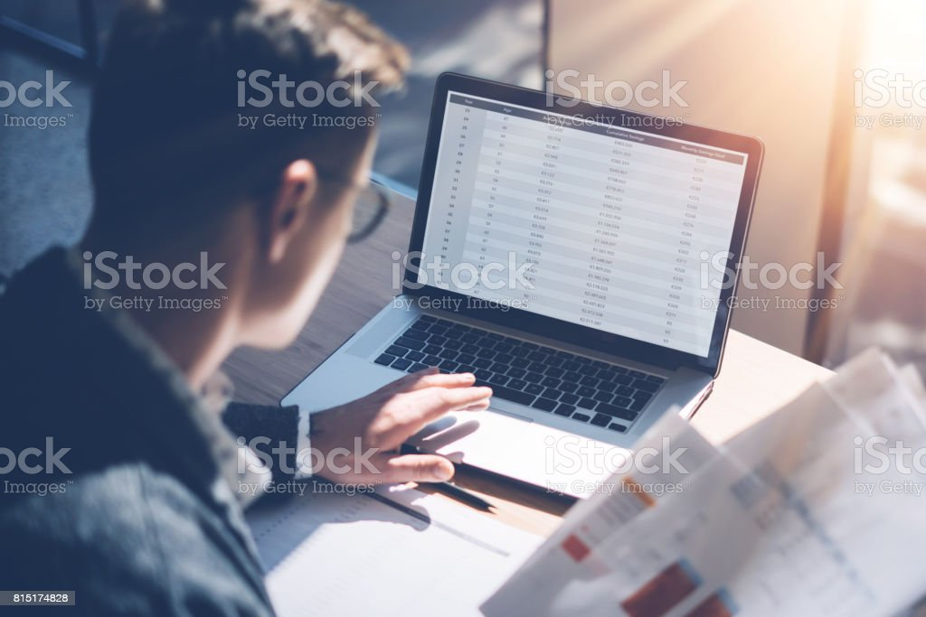Closeup view of banking finance analyst in eyeglasses working at sunny office on laptop while sitting at wooden table.Businessman analyze stock report on notebook screen.Blurred background,horizontal. stock photo