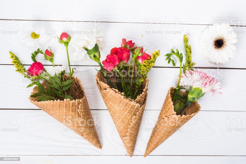白い木製の背景に花とワッフル コーンを持つ美しい花の組成のクローズ アップ ビュー ロイヤリティフリーストックフォト