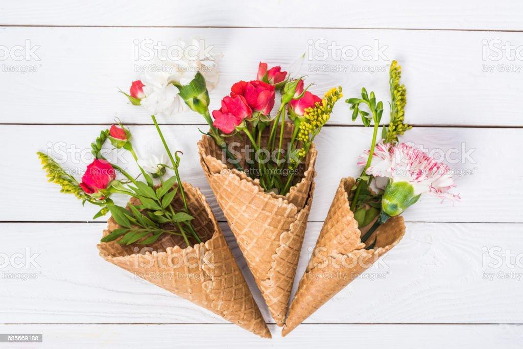 흰색 나무 바탕에 아름 다운 꽃 구성 꽃과 와플 콘의 클로즈업 보기 royalty-free 스톡 사진
