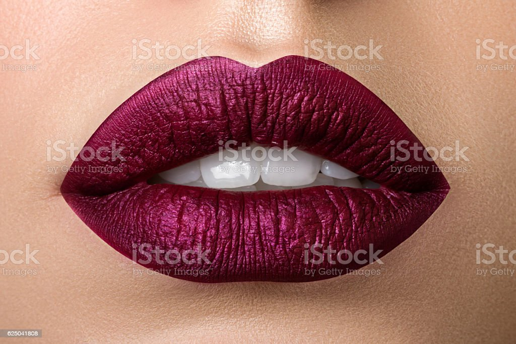 Closeup view of beautiful woman lips with purple matt lipstick stock photo
