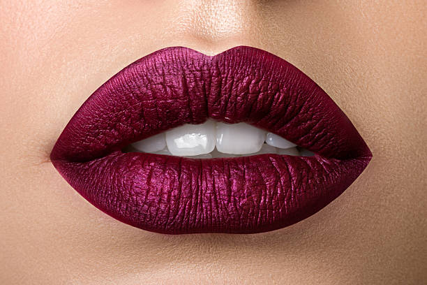 closeup view of beautiful woman lips with purple matt lipstick - human lips stock photos and pictures