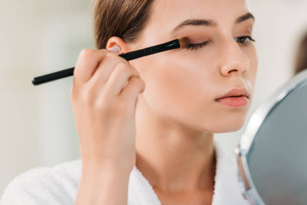 close-up view of beautiful young woman applying eyeshadow with brush close-up view of beautiful young woman applying eyeshadow with brush serbia and montenegro stock pictures, royalty-free photos & images
