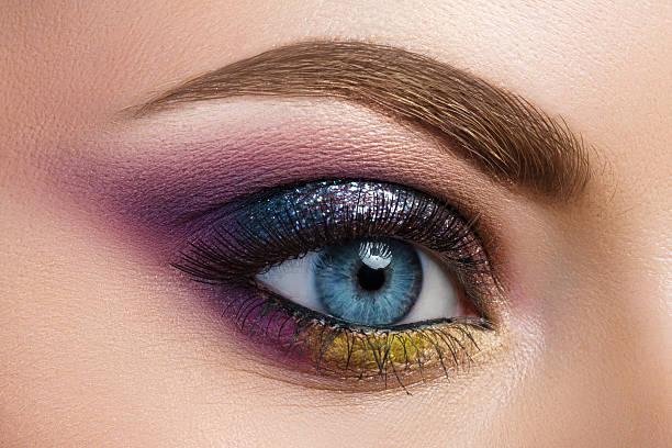 nahaufnahme von blau frau auge mit blick auf die wunderschöne moderne kreative - lila augen make up stock-fotos und bilder