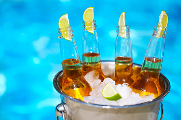 Closeup view of bucket with ice cubes, beer bottles and lime slices stock photo