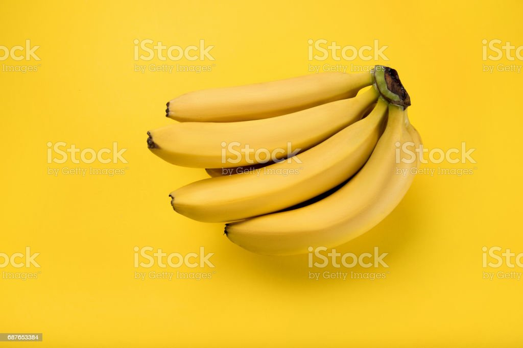 Close-up view of bunch of fresh ripe bananas isolated on yellow 스톡 사진