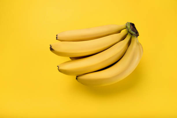 Close-up view of bunch of fresh ripe bananas isolated on yellow stock photo