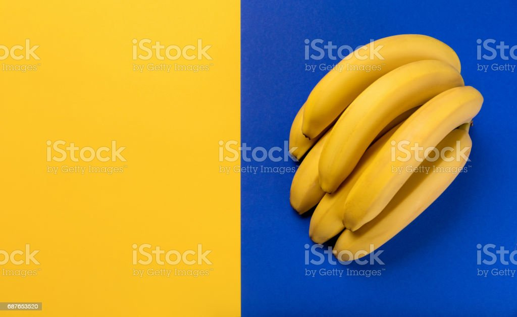 Close-up view of bunch of fresh ripe bananas on blue and yellow background stock photo