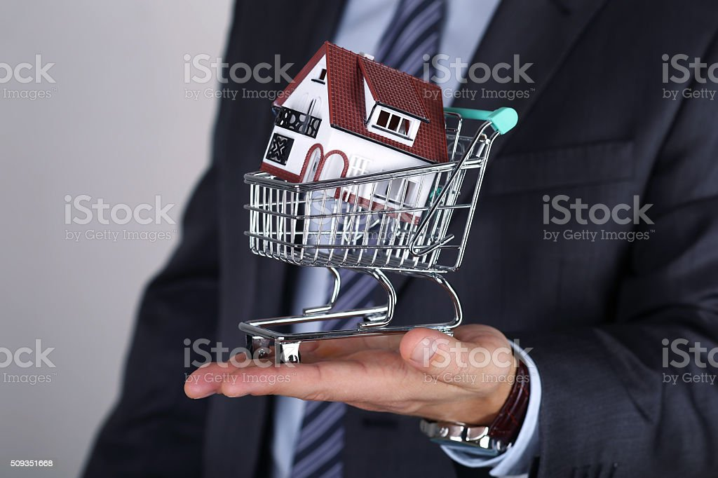 Close-up view of business man's hand holding shopping cart wit stock photo