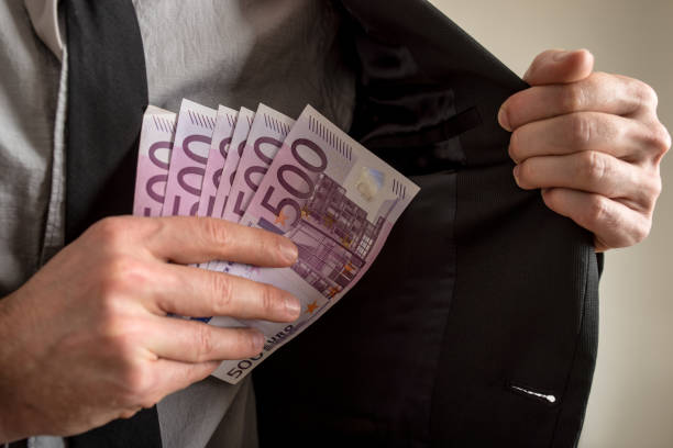 Closeup view of businessman hiding Euro bills in his pocket stock photo