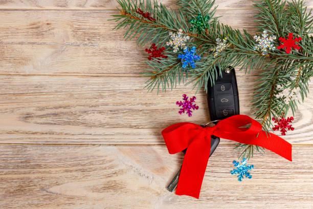 nahaufnahme von autoschlüsseln mit roter schleife als geschenk auf hölzernen hintergrund - schlüssel dekorationen stock-fotos und bilder