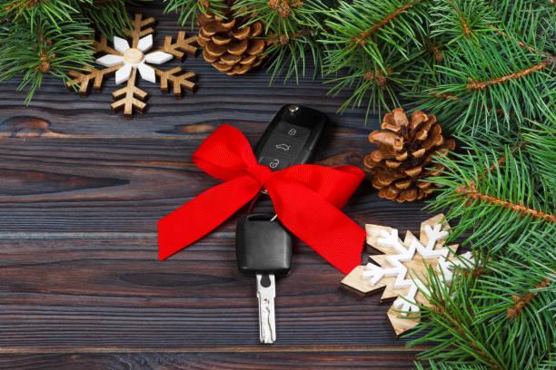 nahaufnahme von autoschlüsseln mit roter schleife als geschenk auf hölzernen hintergrund - autoschleifen stock-fotos und bilder