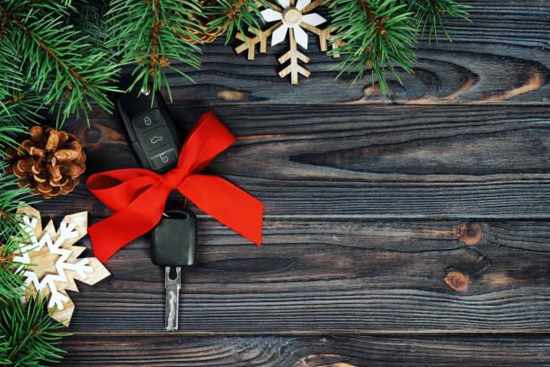 nahaufnahme von autoschlüsseln mit roter schleife als geschenk auf holz vintage-hintergrund - autoschleifen stock-fotos und bilder