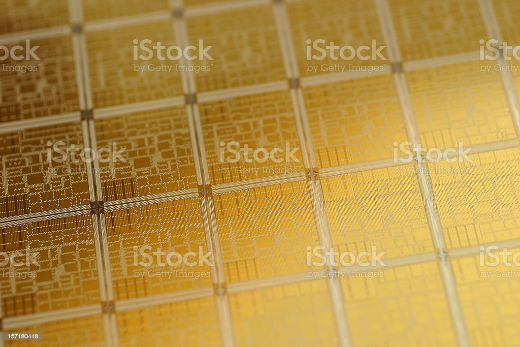 Close-up view of chip wafer with regular pattern in gold stock photo