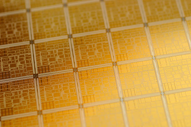 Close-up view of chip wafer with regular pattern in gold  silicon stock pictures, royalty-free photos & images