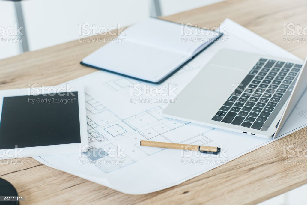 close-up view of digital tablet, blueprint, laptop and notebook on table royalty-free stock photo