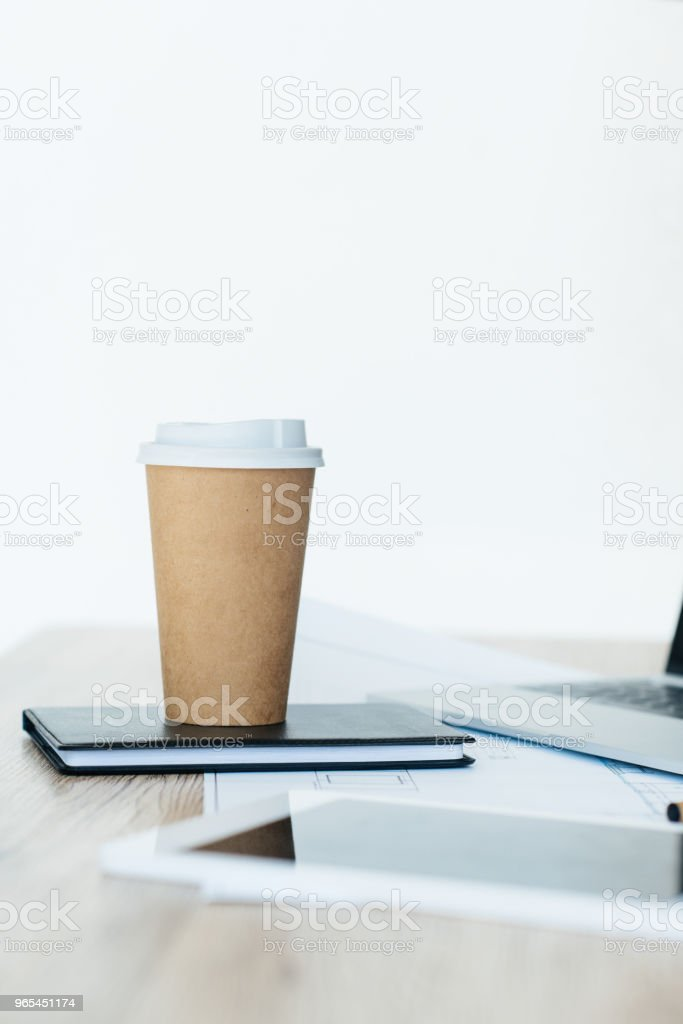 close-up view of disposable coffee cup on notebook, laptop and digital tablet on table royalty-free stock photo