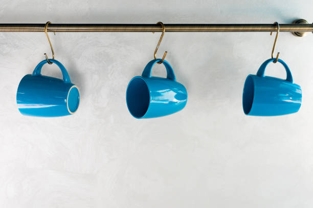 close-up view of empty blue cups hanging in kitchen stock photo