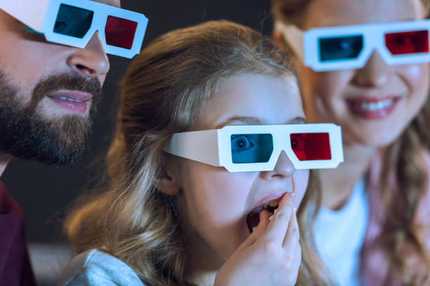 Close-up view of family wearing 3d glasses watching movie and eating popcorn stock photo